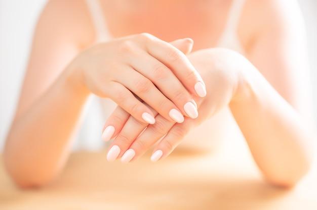 성인 여성 손의 아름답고 단정한 손. 나무 테이블에 중년 여성 팜입니다. 위생 및 손 관리. 뷰티 산업 개념입니다. 미용실에서 전문 매니큐어