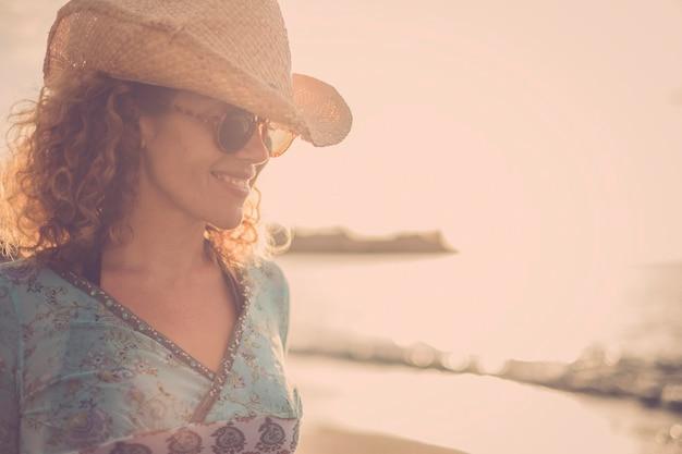 カウボーイハットの笑顔と黄金の夕日を背景にビーチでポーズをとって美しくて素晴らしい金髪の巻き毛モデルの中年。色と自由の独立強い女性の概念