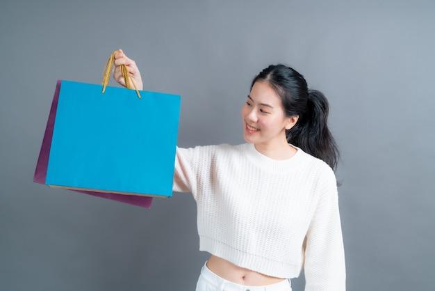 Красивая и молодая азиатская женщина, держащая хозяйственные сумки на серой стене