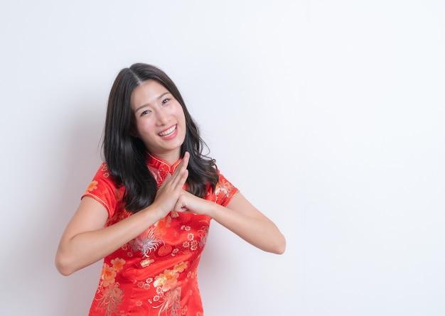 Красивая и молодая азиатская женщина носит красное китайское традиционное платье и улыбается на белом