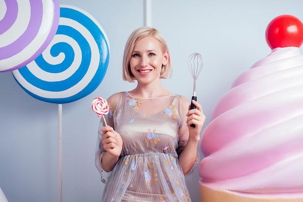Красивая и молодая блондинка сексуальная модель кондитер в платье, идеальный макияж держит венчик и леденец на палочке поддельные сладости, фон конфеты в студии. концепция приготовления аке и кондитерских изделий.