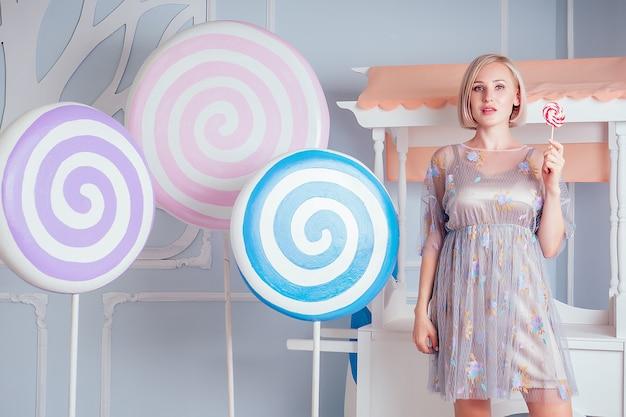 スタジオで赤白甘い高カロリーロリポップ偽のお菓子の背景を手に持っているシックなショートドレスの美しく若いブロンドの女性のセクシーなモデル。食事療法と糖尿病の概念。