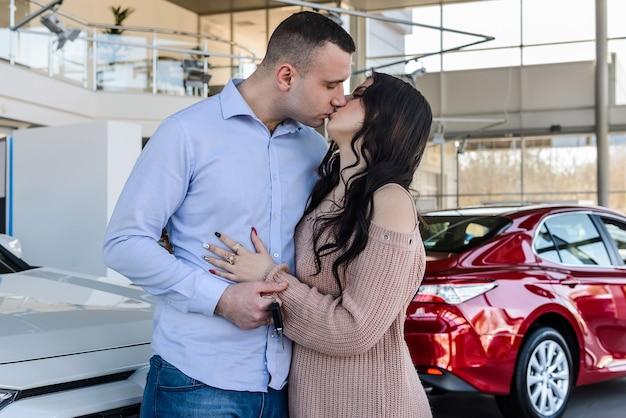 サロンで車のキーを持つ美しく若いカップル