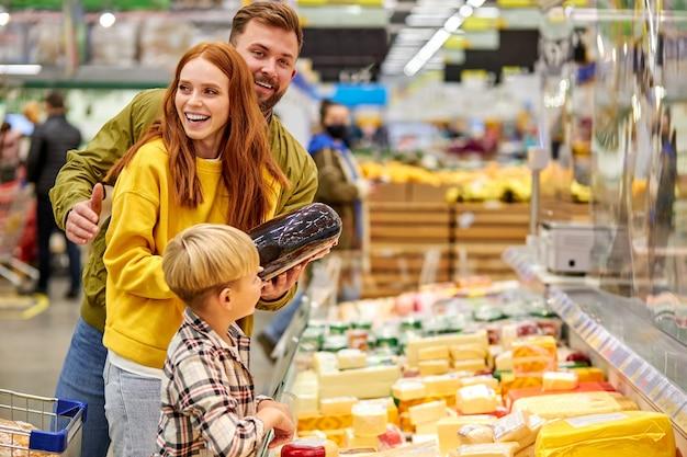 Красивая и молодая семья вместе делает покупки
