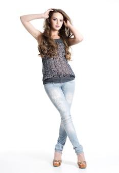 白で隔離ポーズポーズのカジュアルな服を着た美しい少女。スタジオでポーズをとるファッションモデル