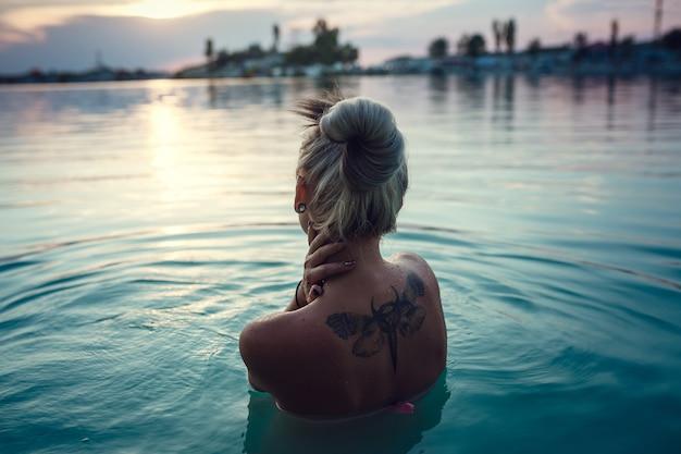 湖に沈む夕日の美しい若い女性。大変な一日の後の夜の休息。乳白色の青い湖の水と美しい夕日