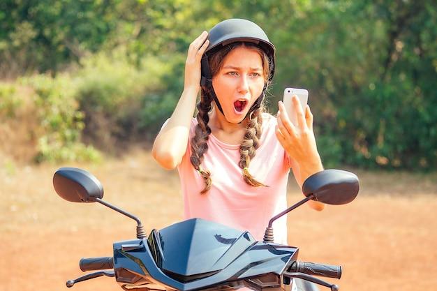 バイク(自転車)に座って電話を見て安全ヘルメットをかぶった美しく若い女性。スクーターと事故を安全に運転するという概念