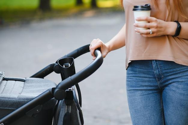 公園を歩いているベビーカーで美しく若い女性の母と赤ちゃん