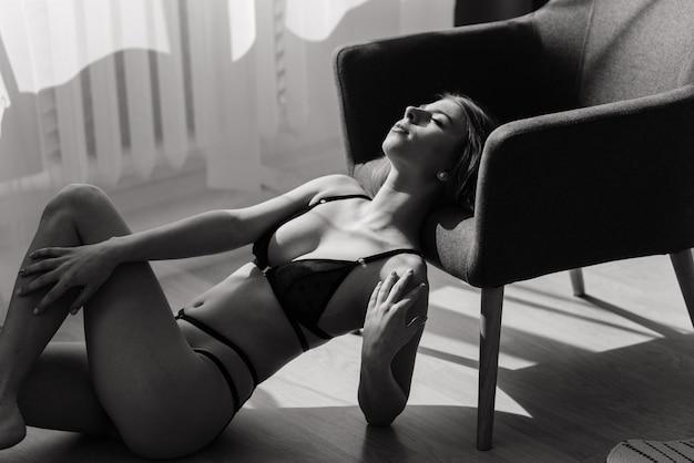 검은 섹시 란제리에 포즈를 취하는 아름 답 고 젊은 여자. 빈티지 인테리어와 복고풍 배경입니다.