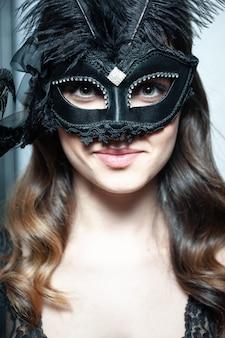 섹시 란제리와 베네치아 마스크에서 포즈를 취하는 아름답고 젊은 여자