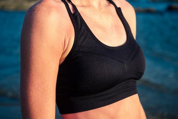 아침에 아름다운 검은색 스포츠 탑에 서 있는 아름답고 젊은 여성