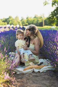 Красивая и молодая женщина со своим милым маленьким сыном в лавандовом поле