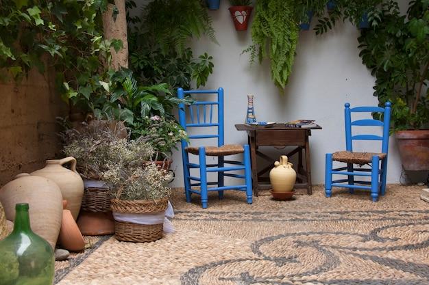 モザイクの石の床に置かれた植物、青い椅子、木製のテーブルと花瓶のある美しいアンダルシアのパティオ。コルドバ、アンダルシア、スペイン。