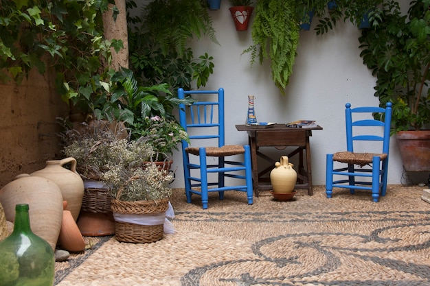 Beautiful andalusian patio with plants, blue chairs, wooden table and vases placed on a mosaic stone floor. cordoba, andalusia, spain.