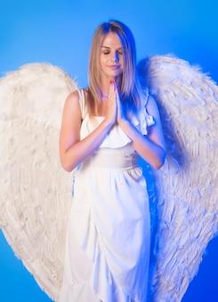 Красивая женщина-ангел с белыми крыльями молится