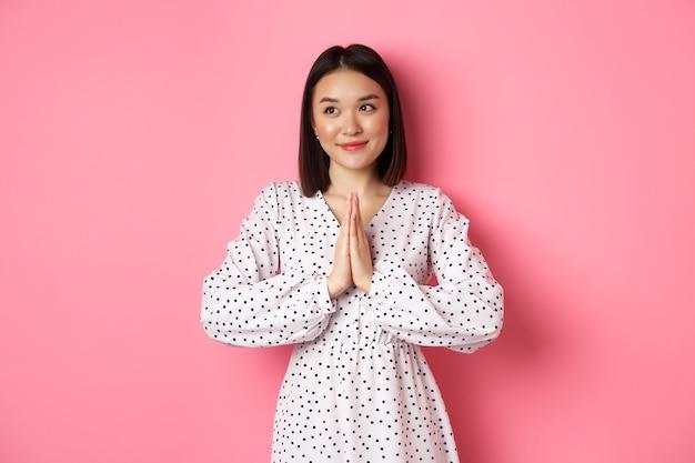 Красивая ангельская азиатская женщина улыбается, взявшись за руки в молитве и смотрит влево на копировальное пространство невинным милым взглядом, стоя на розовом фоне