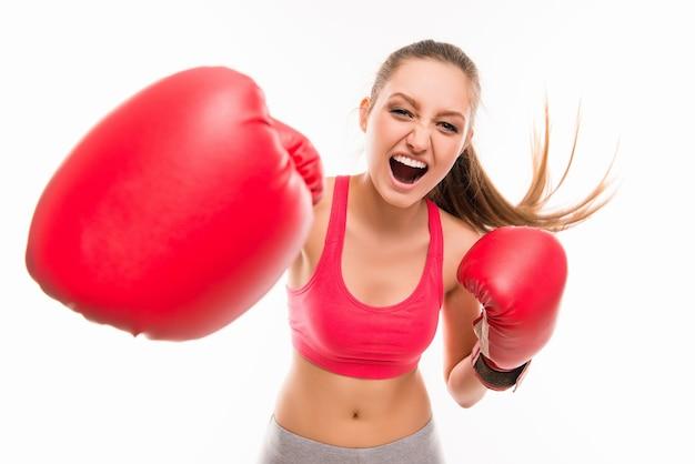赤いボクシンググローブで美しい怒っているスポーツウーマン