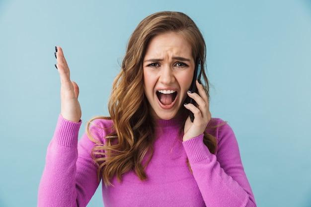 캐주얼 옷을 입은 아름다운 화난 어린 소녀가 파란 벽에 격리되어 휴대전화로 통화하고 있습니다.