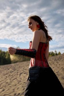 모래에 아름다운 애니메이션 여자. 소녀의 몸에 빨간 코르셋. 얼굴에 밝은 붉은 화장