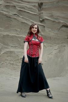 砂の中の美しいアニメの女性。女の子の体に赤いコルセット。顔に真っ赤な化粧