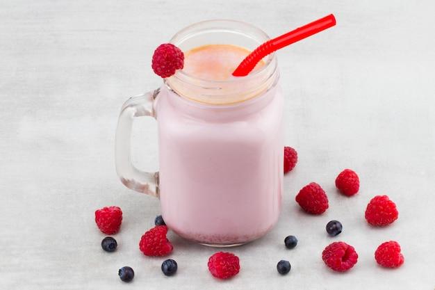 Красивая закуска розовая малина и смузи фруктов черники или молочный коктейль в стеклянной банке с фоном ягод. йогуртовый коктейль. закройте вверх.