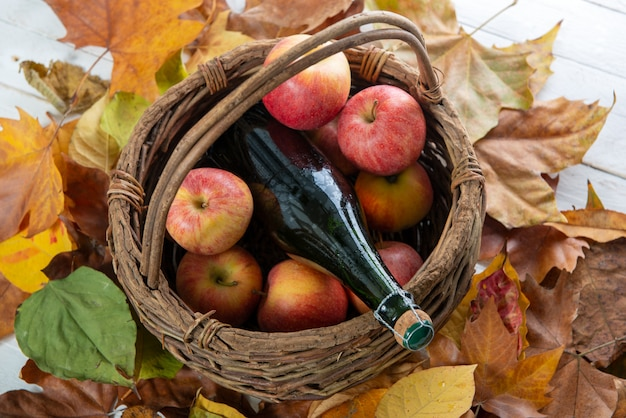 Beautiful apples and bottle of cider, on autumn leaves