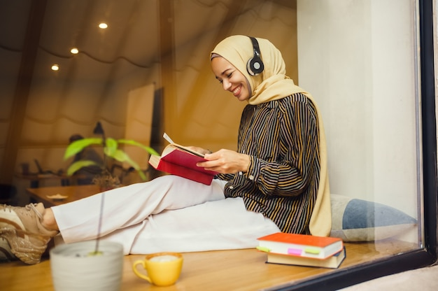 Beautiful arab girl in hijab and headphones in university cafe. muslim woman with books sitting in library.