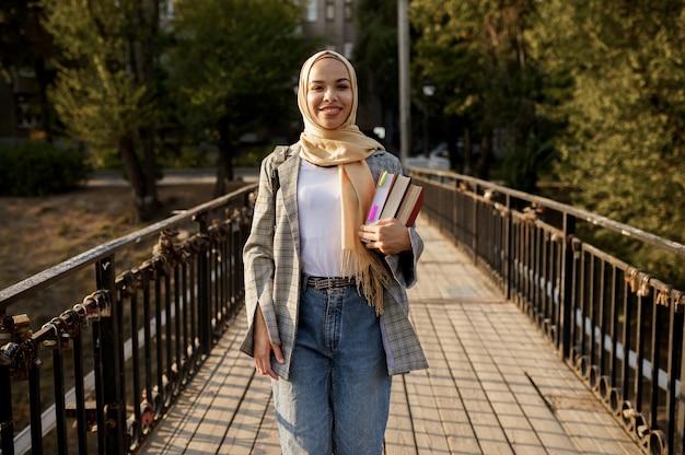 Красивая арабская девушка в хиджабе держит учебники в летнем парке. мусульманская женщина с книгами гуляет в лесу.