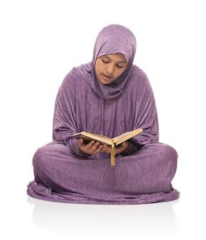 白い背景で隔離のコーランの聖典を読んで座っているイスラムのファッションドレスの美しいアラブのイスラム教徒の少女
