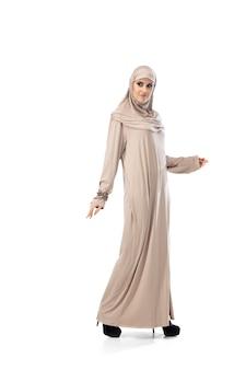 스튜디오 배경에 격리된 세련된 히잡을 입고 포즈를 취한 아름다운 아랍 여성. 패션 컨셉