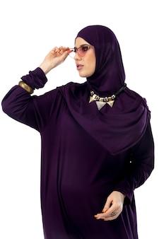스튜디오 배경 패션 컨셉에 격리된 세련된 히잡을 입고 포즈를 취한 아름다운 아랍 여성