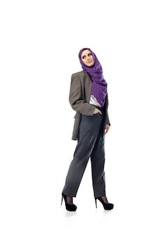 스튜디오 배경 패션 컨셉에 격리된 세련된 사무실 복장으로 포즈를 취한 아름다운 아랍 여성