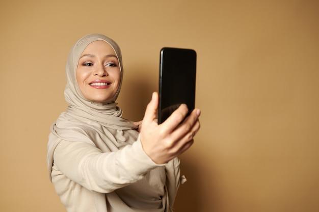 美しい歯を見せる笑顔と覆われた頭を持つ美しいアラブの女性は、コピースペースでベージュの表面に立って自分撮りをします