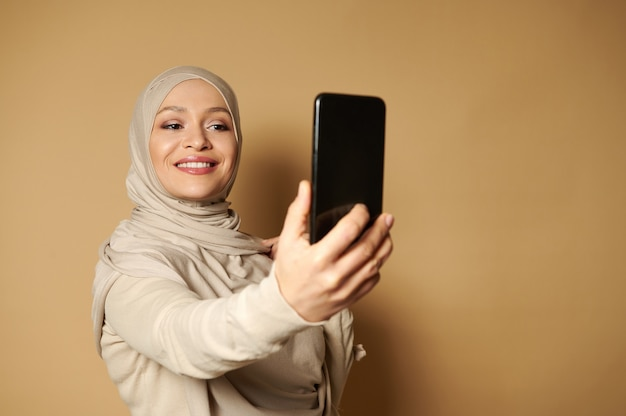 Beautiful arab woman with beautiful toothy smile and covered head making selfie standing against a beige surface with copy space