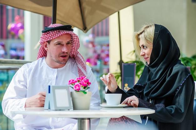 ビンテージインテリアで議論を持っている美しいアラビアカップル、カフェでコーヒーを飲みながら話しているアラビアのカップル