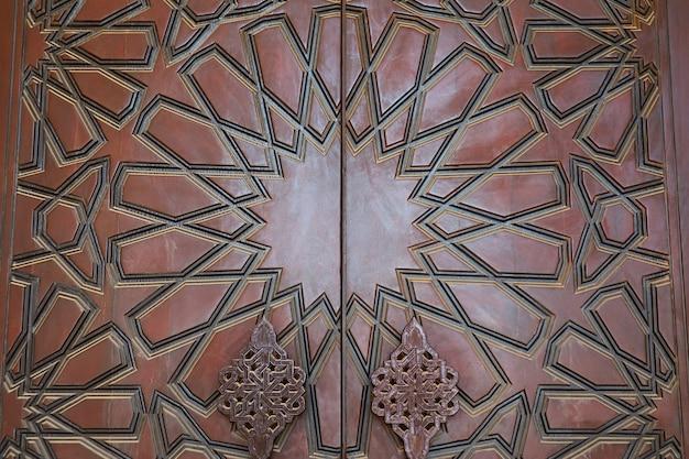 マナーマのモスクの木製ドアの美しいアラビアのパターン