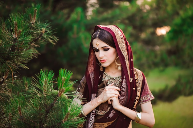 Beautiful arabian woman portrait. young hindu woman with mehndi tattoos from black henna on her hands
