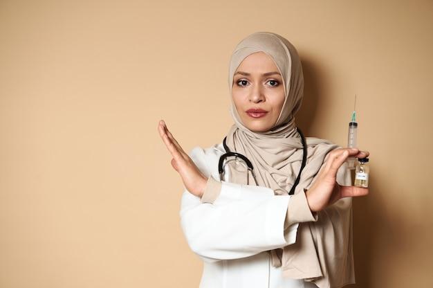 아름 다운 아랍 여성 의사 hijab 몸짓 중지, 주사기와 백신 유리 병을 손에 들고.