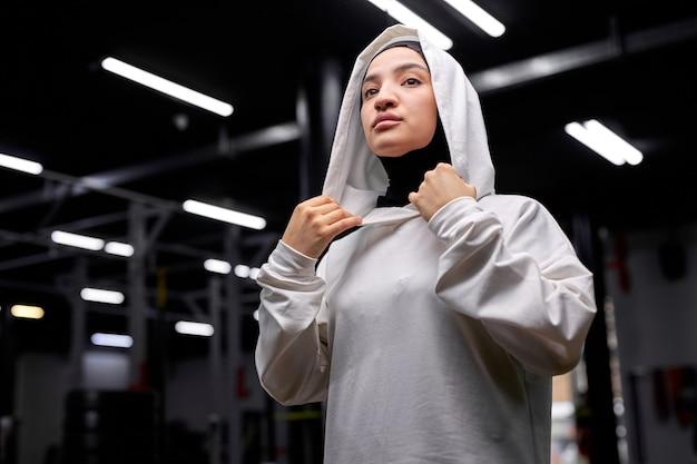 トレーニング後にポーズをとる、横を見て、白いスポーティーなヒジャーブを身に着けている、ヒジャーブの美しいアラビアのイスラム教徒の女性は、力と強さ、幸福の概念を感じて単独で立っています