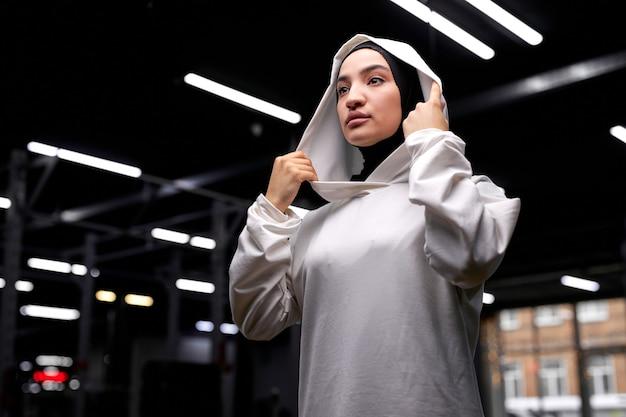 トレーニング前にポーズをとる、横を見る、白いスポーツヒジャーブを身に着けている、ヒジャーブの美しいアラビアのイスラム教徒の女性は、力と強さ、幸福の概念を感じて単独で立っています