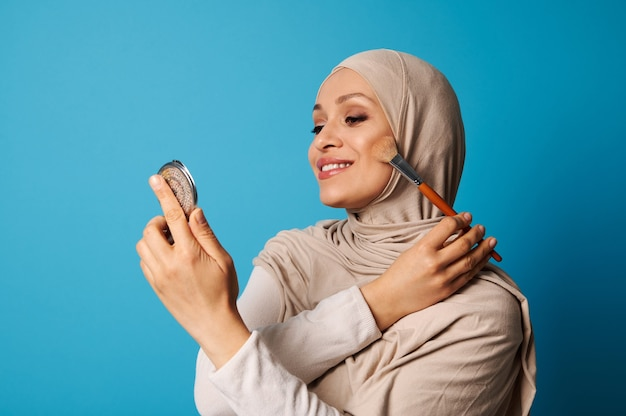 Beautiful arabic muslim woman in hijab holds a cosmetic mirror and a makeup brush and applies blush to the cheekbones of her face, isolated