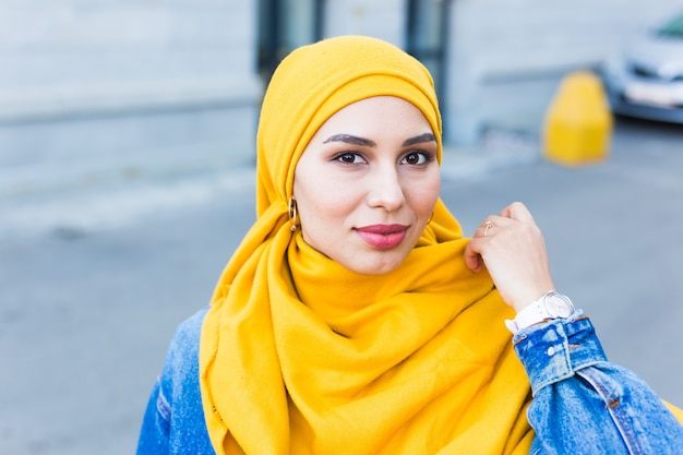 Beautiful arabic muslim woman wearing yellow hijab, stylish female face portrait over city street.