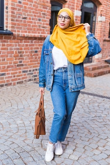 Beautiful arabic muslim woman wearing yellow hijab, stylish female portrait over city street.