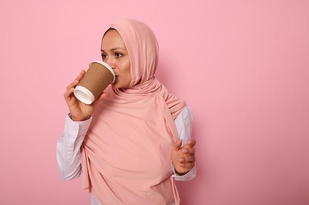 1회용 판지 테이크아웃 컵에서 뜨거운 음료, 차 또는 커피를 마시는 머리를 덮은 아름다운 아랍 이슬람 여성, 복사 공간이 있는 분홍색 배경에 대해 옆으로 서 있는 3/4