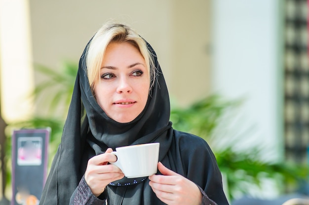 コーヒーを飲みながらレストランでアラビア語美人。アラビア風ファッション。ヒジャーブとアバヤを着てレストランに座っている中東の女性。朝ごはん