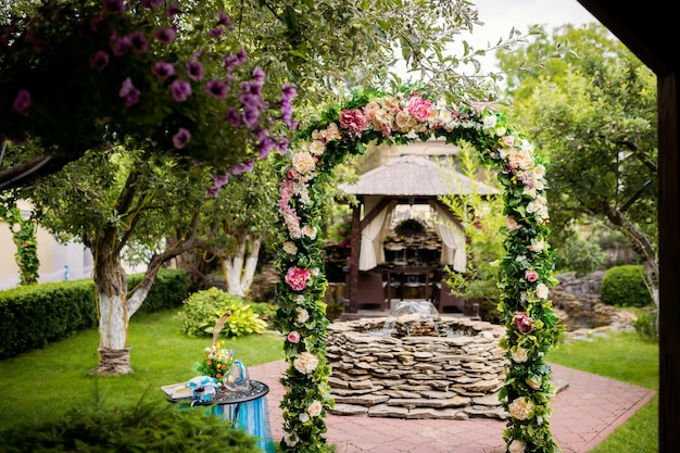 Beautiful arch decorated with colorful flowers on the background of a small fountain outdoors.