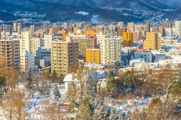 Красивая архитектура здания с горным ландшафтом в зимний сезон, город саппоро, хоккайдо, япония