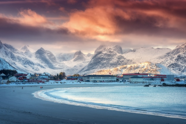 Beautiful arctic sandy beach with blue sea in winter at sunset