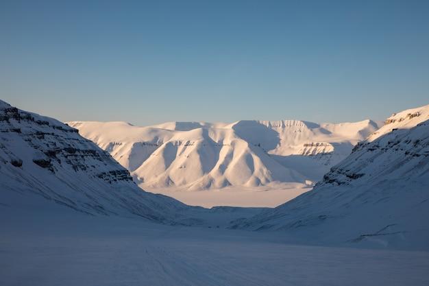 Красивый арктический зимний пейзаж со снегом покрыл горы замороженным фьордом биллефьорден. шпицберген, норвегия