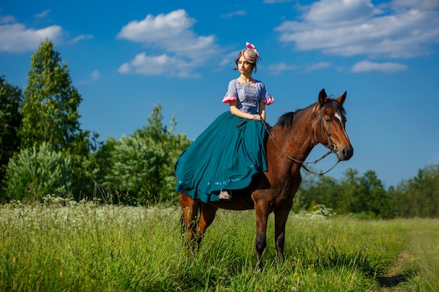 Beautiful aristocrat in a dress on a horse